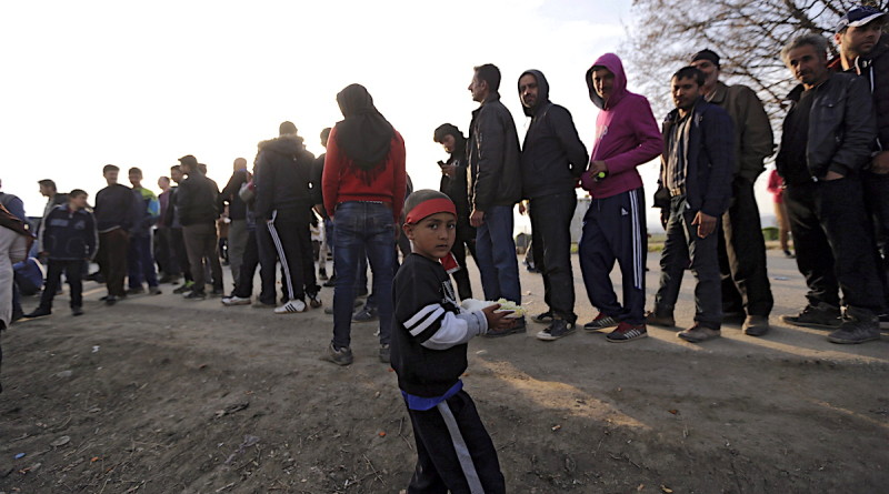 epa05224506 A migrant child walks away with food received as others line up at the Greek-Macedonian border, in Idomeni, Greece, 21 March 2016. Migration restrictions along the so-called Balkan route, the main path for migrants and refugees from the Middle East to the EU, has left thousands of migrants trapped in Greece EPA/ARMANDO BABANI +++(c) dpa - Bildfunk+++